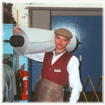 Andrew Martin carrying a roll of woven material at Masson