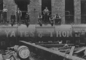 Large boiler with wording 'Yates & Thom Ltd' and 8 workmen sitting or standing on top.